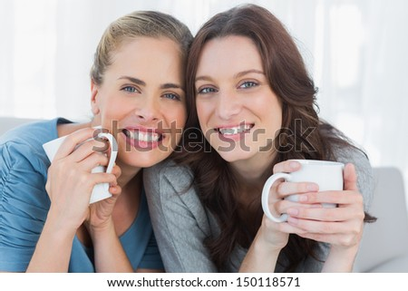 Smiling women holding their cup of coffee sitting on the sofa