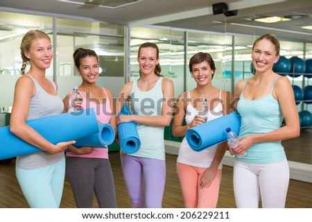Smiling women in fitness studio before yoga class at the leisure center - stock photo