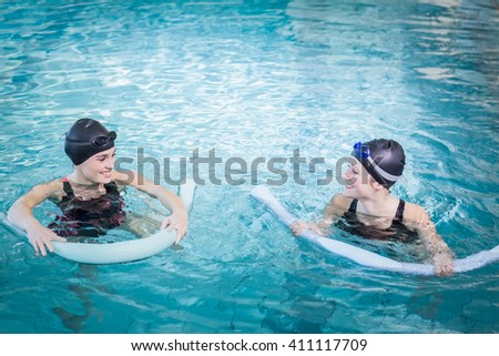 Smiling women in the pool with foam rollers at the leisure center - stock photo