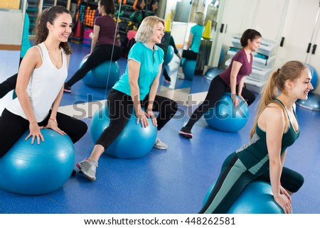 smiling women jumping on exercise ball during group train - stock photo