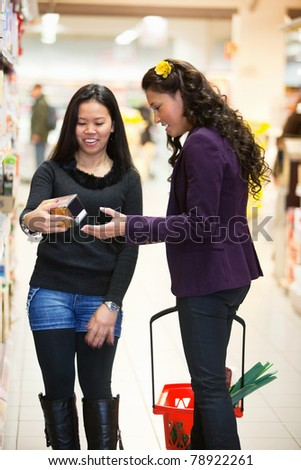 Smiling women looking at a product in a shopping store with people in the background - stock photo