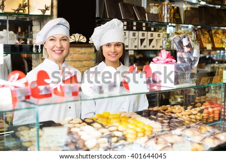 Smiling women selling fine chocolates and sweet pastry in coffee-house