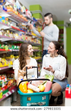 Smiling women standing near shelves with canned goods at shop