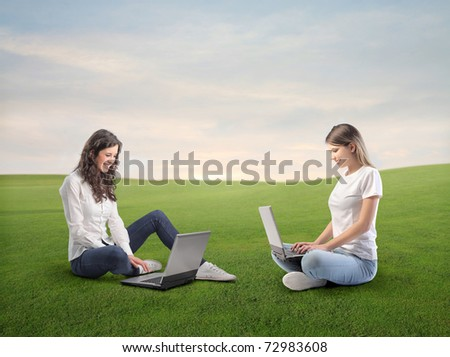 Smiling women using laptops on a green meadow - stock photo