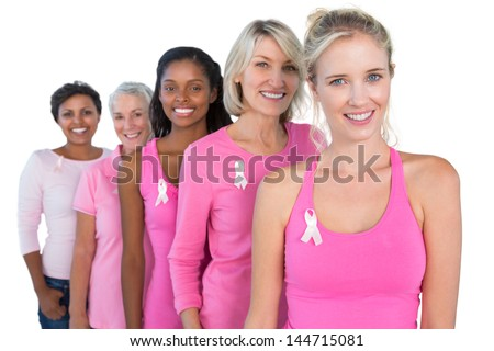 Smiling women wearing pink and ribbons for breast cancer on white background - stock photo