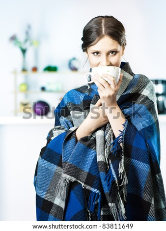 smiling women with blanket wrapped around in kitchen - stock photo