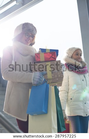 Smiling women with gifts and shopping bags by window during winter - stock photo