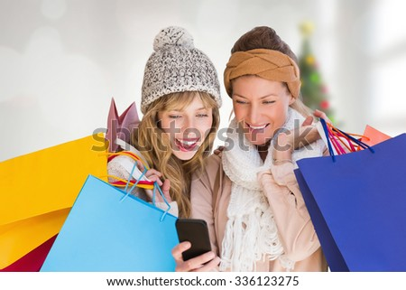 Smiling women with shopping bags looking at mobile phone against blurry christmas tree in room - stock photo