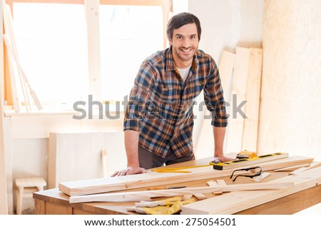 Smiling woodworker. Cheerful young male carpenter leaning at the wooden table with diverse working tools laying on it - stock photo