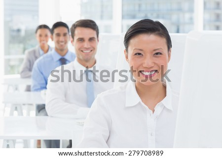 Smiling work team using computer in office
