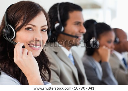 Smiling worker doing her job with a headset while looking at the camera - stock photo
