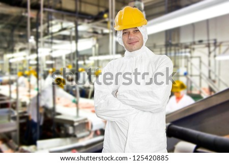 Smiling worker in a meat processing factory and slaughterhouse, wearing hygienic clothing - stock photo