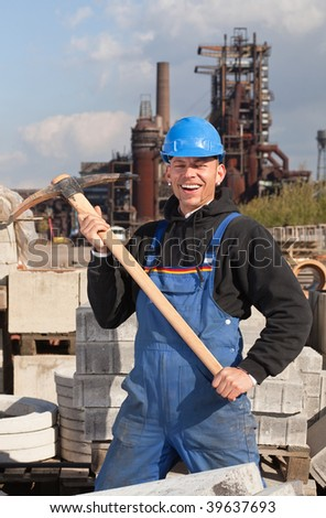 Smiling worker in blue hard hat standing against industrial background
