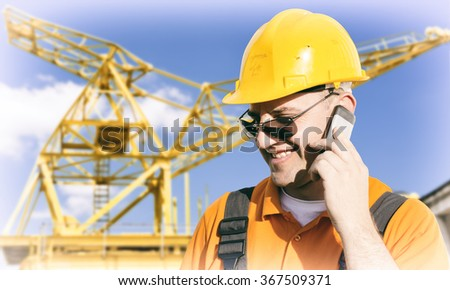 Smiling worker in protective uniform and protective helmet in front of construction crane - toned image, retro film filtered in instagram style