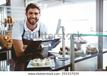 Smiling worker posing behind the counter at the bakery - stock photo