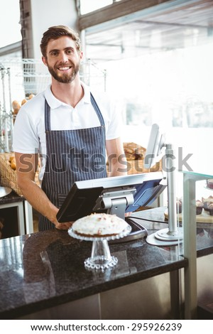 Smiling worker posing behind the counter at the bakery