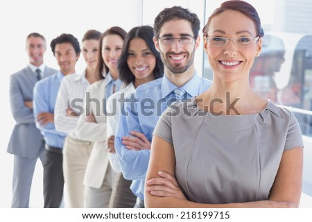 Smiling workers in a line looking at the camera - stock photo
