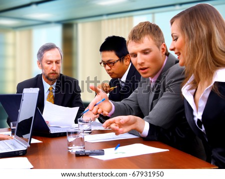 Smiling working people sitting at the business meeting in office - stock photo