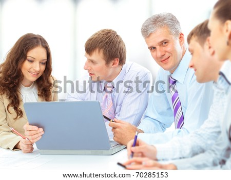 Smiling working people sitting at the business meeting in office