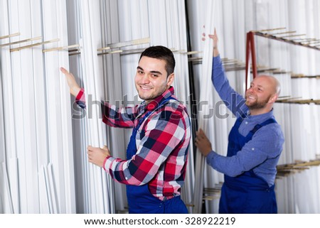 Smiling workmen choosing PVC window profile at factory - stock photo