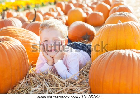 smiling 6-year old boy having fun and enjoying autumn time at pumpkin patch - stock photo