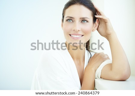 Smiling 30 year old woman at the window. Fresh light blue background. - stock photo
