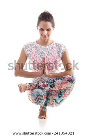 Smiling yoga girl on white background squatted down with palms touching in a gesture of namaste - stock photo