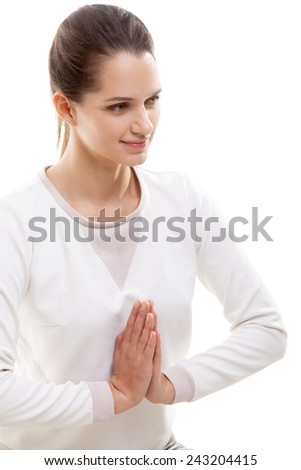 Smiling yoga girl on white background with palms touching in a gesture of namaste - stock photo
