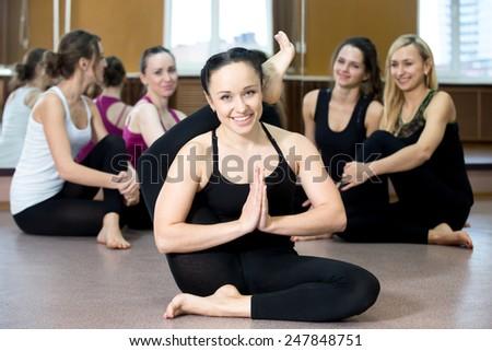Smiling yogi girl in class in Yoga asana, exercising, stretching - stock photo