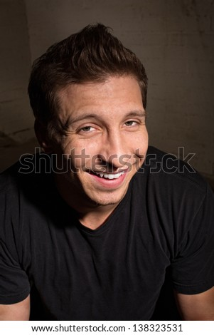 Smiling young adult male in black shirt indoors - stock photo