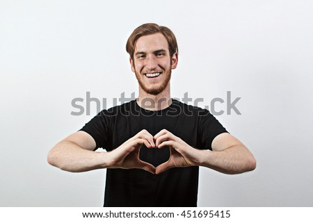 Smiling Young Adult Male in Dark T-Shirt Gesturing, Forming a Heart with His Thumbs and Fingers - stock photo