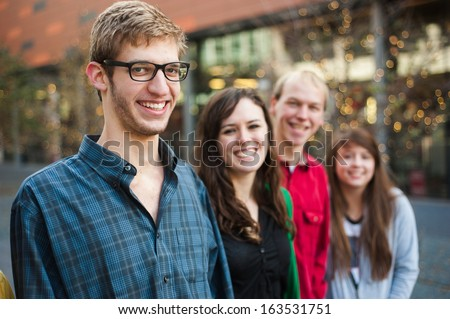 Smiling young adults outside - stock photo