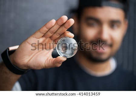 Smiling young African American man holding glass Earth model in hand. Concept for global connection, ecology or planet care. Macro close up, focus on globe  - stock photo