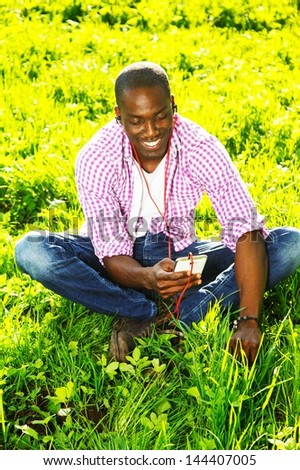 Smiling young african american man in shirt listens music in a park - stock photo