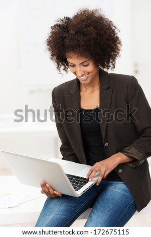 Smiling young African American student with a frizzy afro hairstyle using a laptop balanced on her lap while sitting on a desk smiling as she reads the screen - stock photo