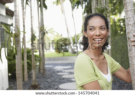 Smiling young African American woman holding on to palm tree - stock photo