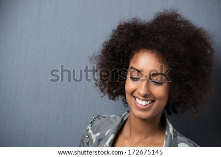 Smiling young African American woman with downcast eyes and a wild afro hairstyle against a dark grey background with copyspace - stock photo