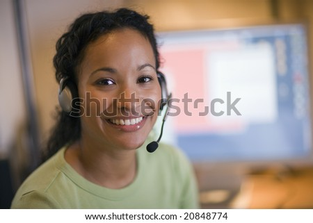 Smiling young African American woman with headset and microphone - stock photo