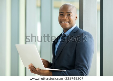 smiling young african businessman using laptop computer indoors - stock photo