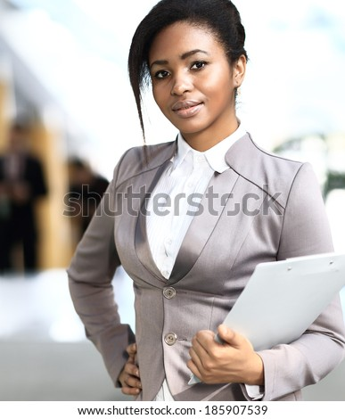 Smiling young african businesswoman in modern office - stock photo