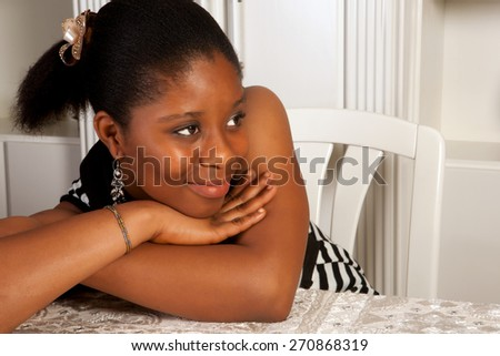 Smiling young african ghanese girl sitting at a table - stock photo