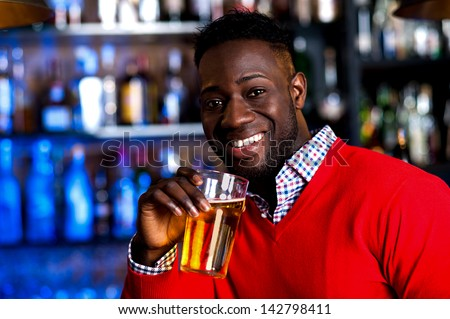 Smiling young african guy enjoying fresh beer at pub.