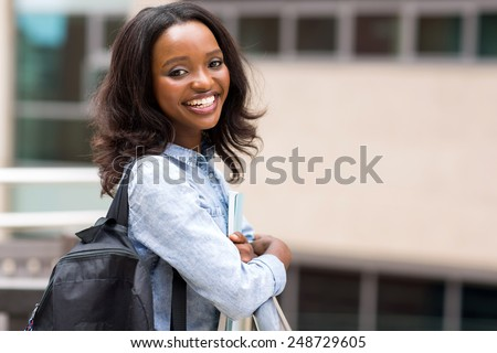 smiling young african university student holding books - stock photo