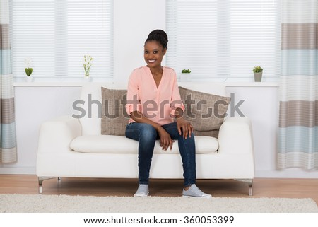 Smiling Young African Woman Sitting On Couch In Living Room