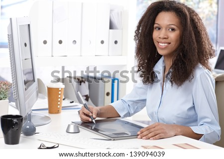 Smiling young afro-american office worker using drawing table, sitting at desk. - stock photo