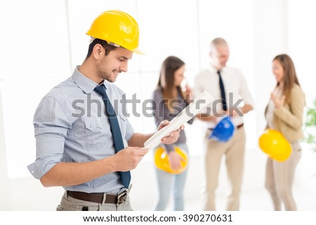 Smiling young arabian architect with helmet standing in the office and analyzing blueprint. His colleagues talking in background. - stock photo