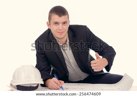 Smiling young architect giving a thumbs up gesture of success and approval as he sits working on a blueprint at a small desk with his hardhat alongside, over white