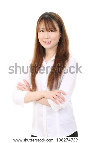 Smiling young asian business woman with arms crossed - stock photo