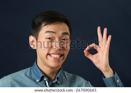 Smiling young Asian man giving okay sign - stock photo