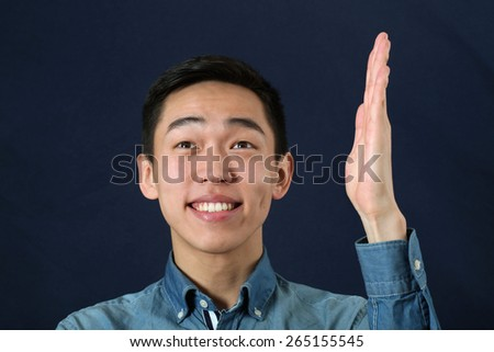 Smiling young Asian man holding his hand upright and looking upward - stock photo